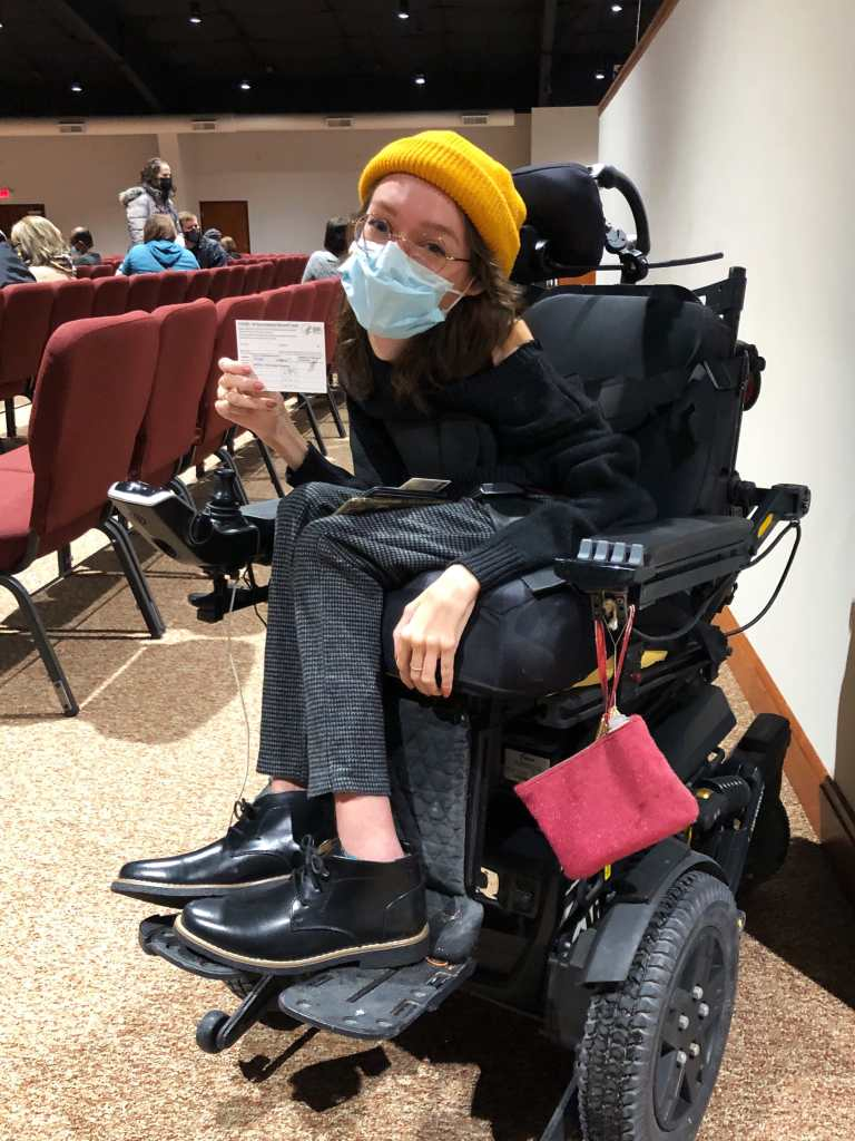 Emily Ackerman, a white woman in a black power wheelchair is holding up her COVID vaccine card. She's wearing a black sweater and boots with grey checked pants, a yellow beanie, and a blue medical mask.