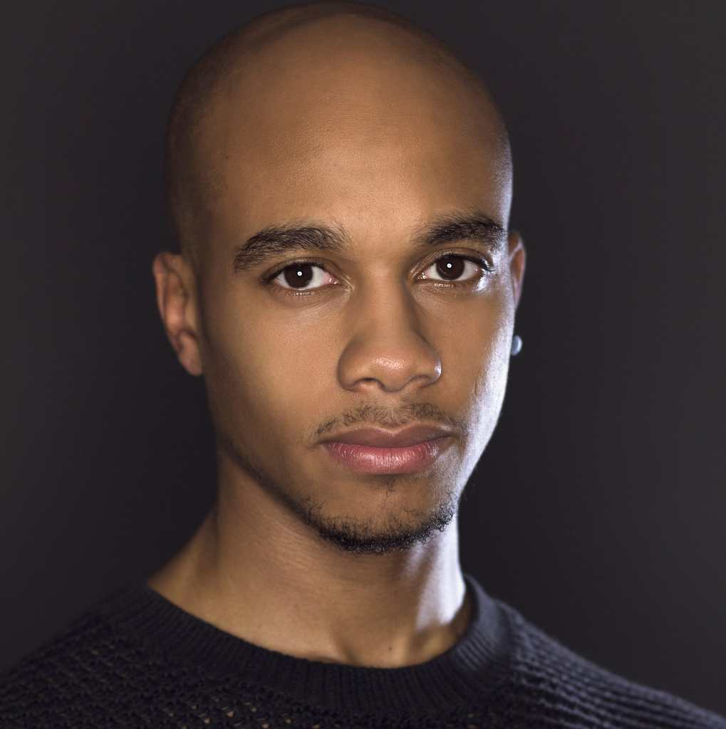 Hari Ziyad, a Black person with a bald head and short facial hair, stands in front of a dark grey background looking into the camera with a slight smile. They are shown from the shoulders up wearing a black knitted sweater, with a black circular earring in their left ear. Photo by Brandon Nick