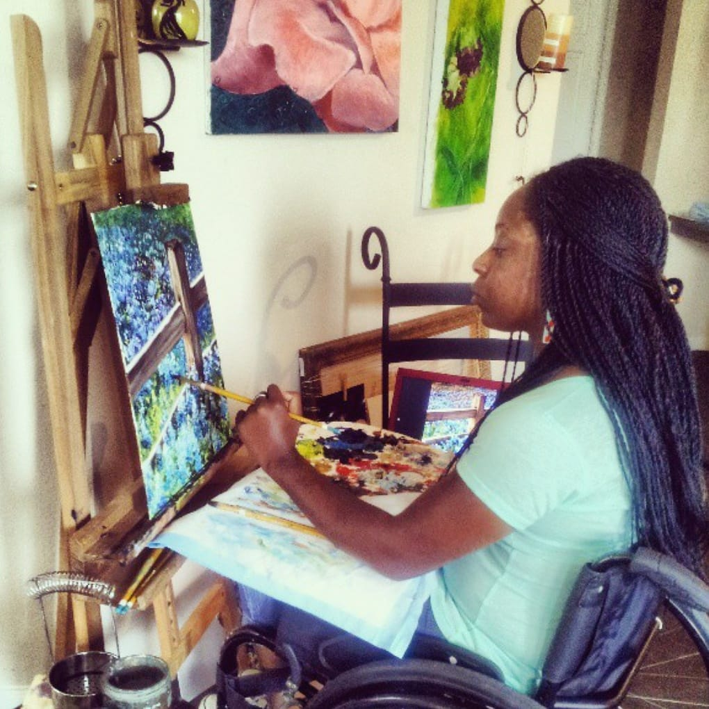 Photo of Kemi Yemi-Ese, a young Nigerian American Black woman with long black braids. Kemi is painting at her easel while sitting in her manual wheelchair. The canvas is of a wooden fence and a field of bright blue-purple flowers.
