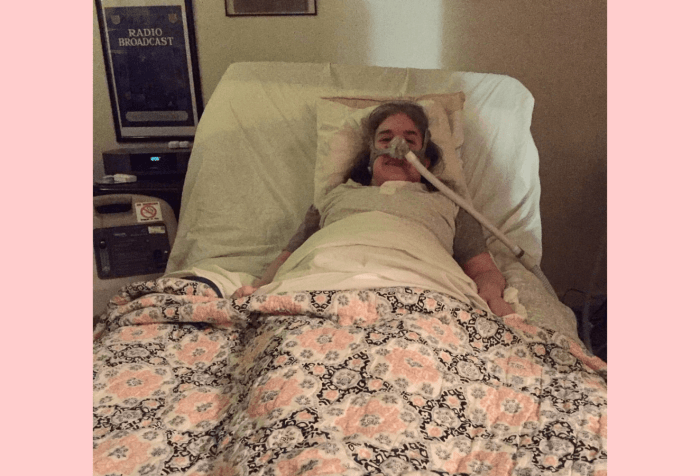 Graphic with a light pink background. In the center, a photo of Ingrid Tischer of her first day home from the hospital. Ingrid is a middle-aged white woman wearing a Bi-Pap mask in a hospital bed under a colorful quilt.