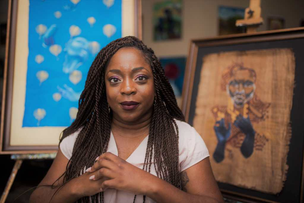 Photo of Kemi Yemi-Ese, a young Nigerian American Black woman with long black braids. She is wearing a white short-sleeved shirt and her hands are clasped in front of her. Behind her are two canvases featuring her paintings, the one on the left is light blue painting with abstract shapes and the one on the right is a painting of an elder Black man