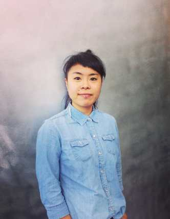 Portrait photo of an Asian American woman looking directly in the camera with a slight half smile. She is wearing a light blue button-up shirt and a long earring on her right ear. She has a lip ring, dark eyes, and dark hair that is tied up with bangs that are cut in a diagonal line, slanting to her left. She is set against a silver background.
