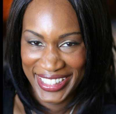 A headshot of Morénike, a dark skinned Black person who is looking at the camera and smiling. Morénike has shoulder length black hair and is wearing a black shirt.