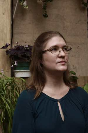 A youngish white woman with chestnut brown hair wearing glasses and a drapey turquoise shirt. She stands in front of a stone wall and potted plants, looking up and away from the camera. Photo credit: Charlie Stern