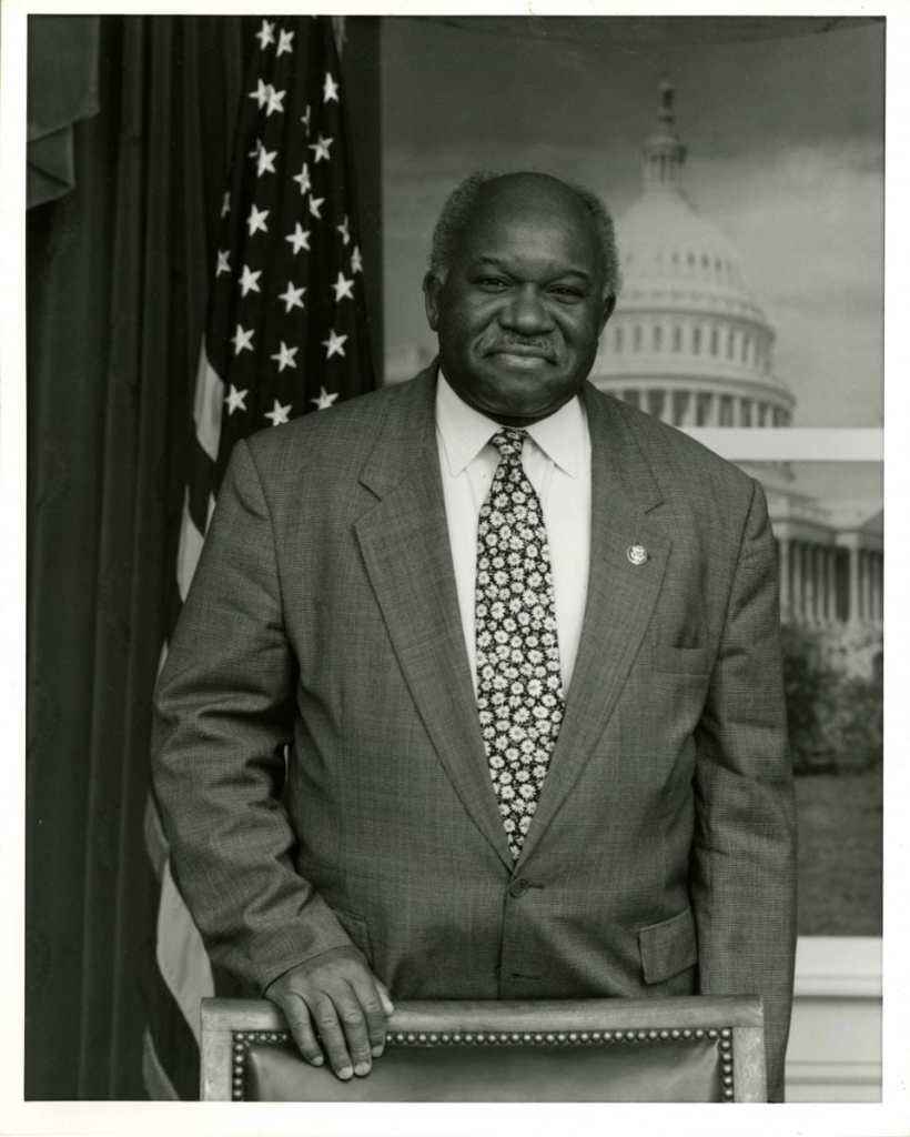 Congressman Major Owens, U.S. House of Representatives, 1983-2006. Major Owens Collection, Brooklyn Public Library – Center for Brooklyn History. Photo of an older Black man who is wearing a suit and tie standing with one hand placed on the back of a chair. Behind him is the American flag on a stand to the left of him and a backdrop showing the US Capitol building. He is smiling at the camera.