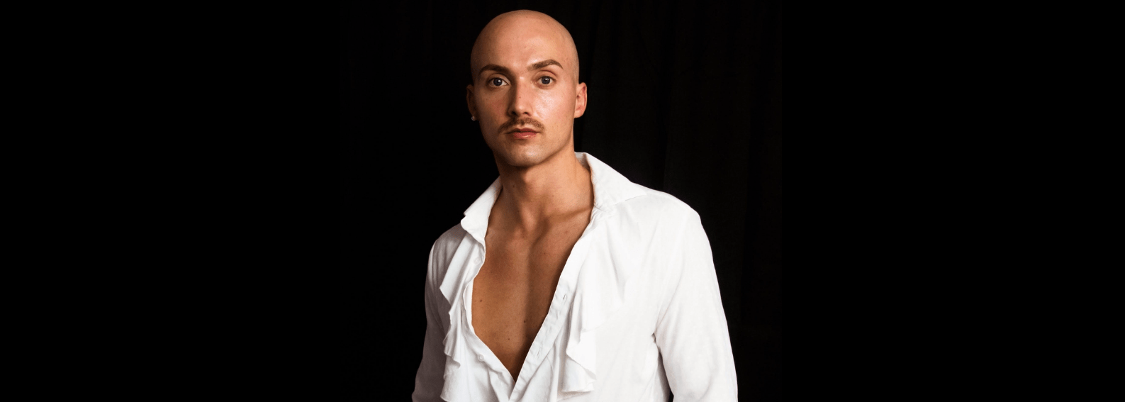J. Logan Smilges, a white gender nonconforming trans person with a mustache, looks toward the camera without smiling. They are wearing a long-sleeve white shirt with ruffles down the middle and black pants with a checkered print. Photo credit: Darius Stokes