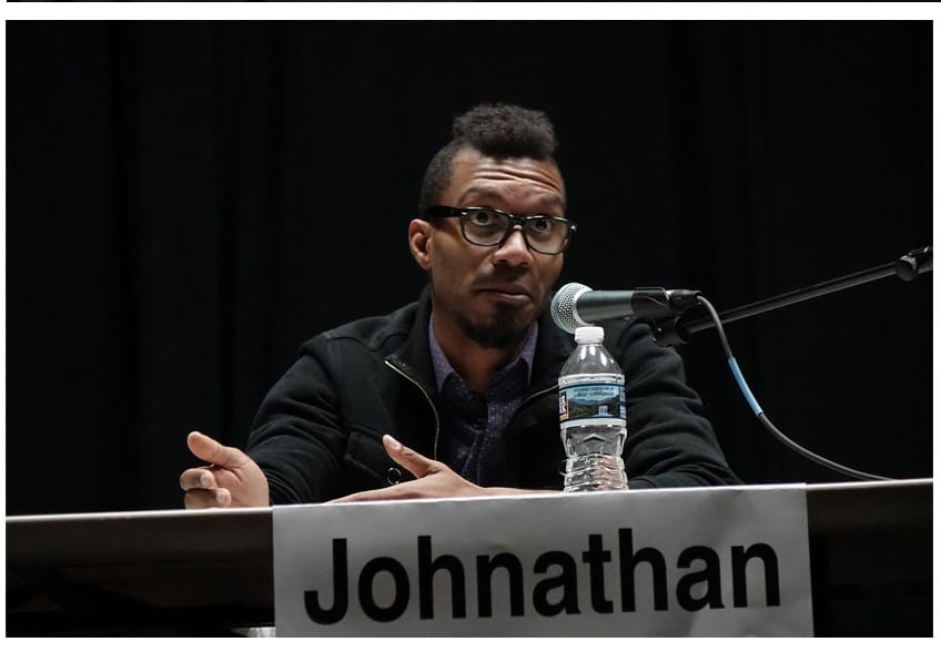 Johnathan, a black man with glasses, is seated at a table behind a microphone. He appears to be using his hands to emphasize his explanation, and his expression is one of challenge. A placard with his name on it and a bottle of water are also on the table.