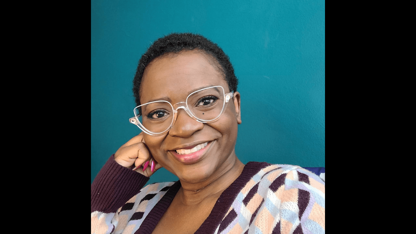 Graphic with a black background with a photo of a Black femalewith dark brown complexion, close cropped black hair, wearing a wide smile, clear plasticglass frames and sweater with a geometricpattern in eggplant, sky blue, white and light peach colors.