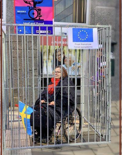 En kvinna som sitter i rullstol inlåst. I buren hänger ett skyllt där det står: Ett projekt finansierad av EU