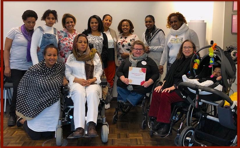 En grupp av kvinnor som står och sitter i rullstol.