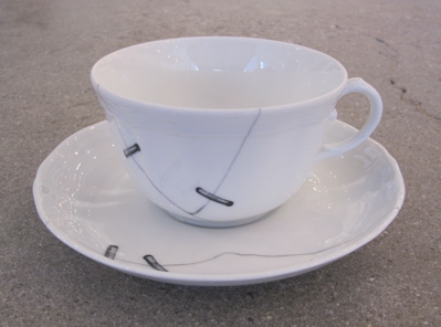 """This is actually a faux repaired tea cup. These were created in 2010 by architect and product designer Paola Navone and feature printed cracks """"repaired"""" with trompe l'oeil metal staples."""