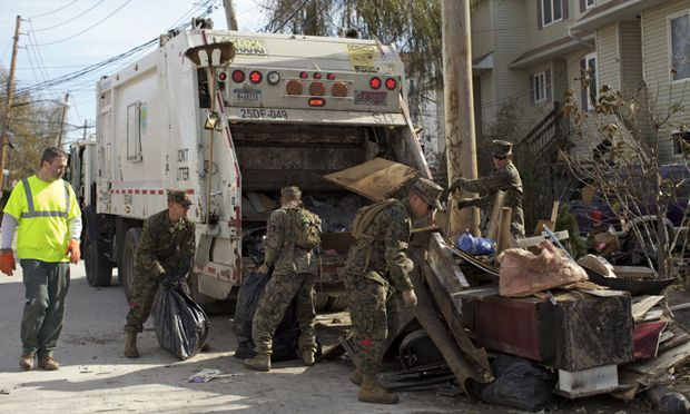 A sanitation worker teams up with members of the National Guard to clear debris in the Midland Beach section of Staten Island. (Amy Pearl/WNYC)