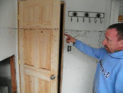 """Original caption: """"Port Monmouth resident Jules Johnson points out how high flood waters from Hurricane Sandy got inside his home."""" Rob Spahr / NJ.com"""
