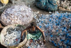 An informal sector waste worker picker sorting through different types of plastics. Photo by Enrico Fabian. Not for republication.