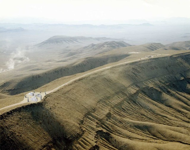 Yucca Mtn with artist's rendition of warning monument for future generations.