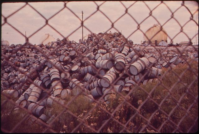 1280px-A_MOUNTAIN_OF_DAMAGED_OIL_DRUMS_NEAR_THE_EXXON_REFINERY_-_NARA_-_546004