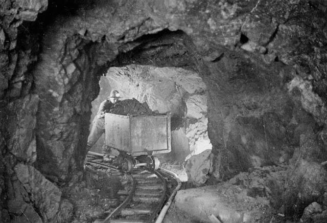 A_miner_hauling_a_car_of_silver_radium_ore,_340_feet_below_the_surface,_Eldorado_Mine_of_Great_Bear_Lake