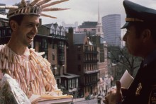 Detail of a person in a statue of liberty costume made of tampon applicators smiling at a police officer