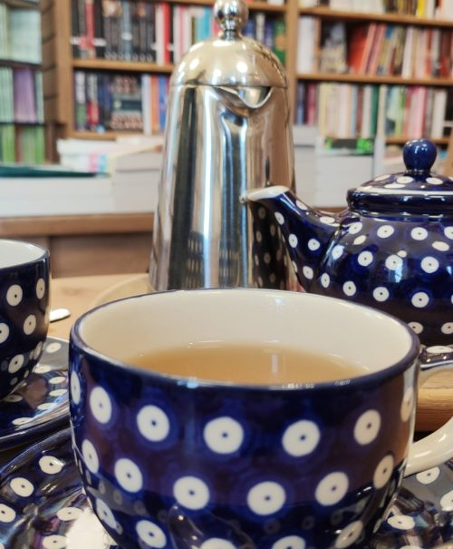 Dark blue spotted porcelain cups sit on a wooden table in front of a colourful shelf of books