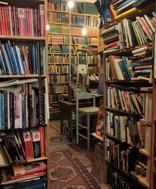 A dimly lit old book shop with floor to ceiling shelves. Books lie on the floors and worn carpets cover the aisles.
