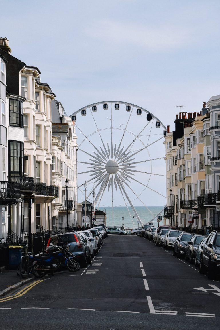 Terrace houses line the sides of a street. A big ferris wheel is stood at the end of the street in front of the ocean