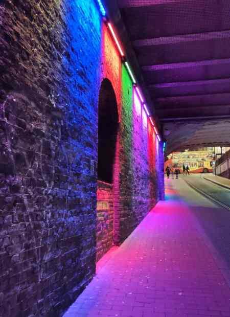 Colourful lights highlight the space under a dark bridge.