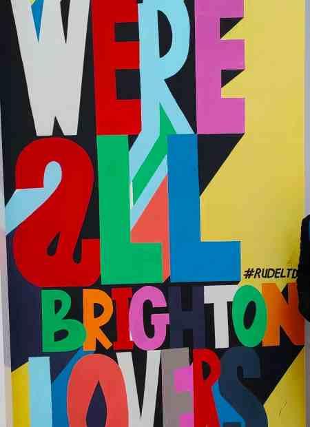 Colourful graffiti reads 'we are all brighton lovers'