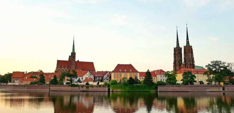 The island of Ostrow Tumski. The Cathedral of St John the Baptist towers rise in the background behind Wroclaw's green trees.
