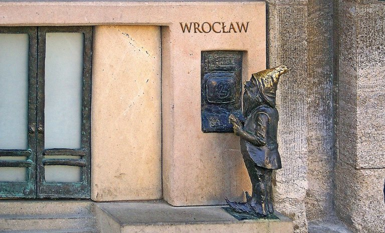 A Wroclaw Dwarf Figure removes cash from a bank