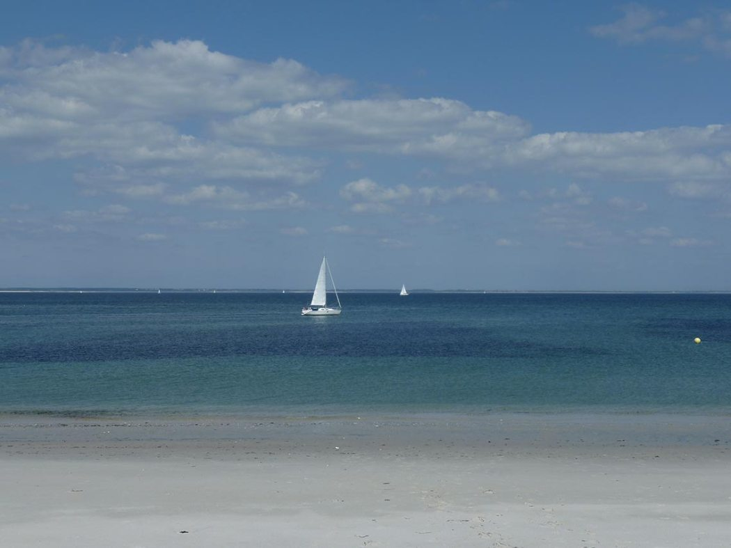 Sailboat cruising past les Grands Sables beach