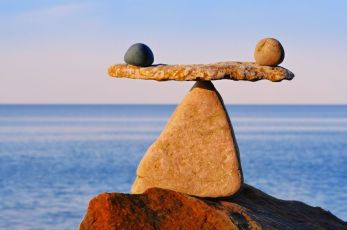 Symbol of scales is made of stones balanced on a boulder