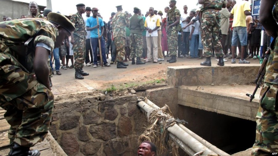 FILE - A man begs for help from the military as he stands in a drain where he had hidden to escape a lynch mob at the Cibitoke district of Burundi's capital, Bujumbura. International judges have approved the opening of a full investigation into alleged crimes against humanity in Burundi, where at least 1,200 people have died in unrest since 2015. Credit/VOA