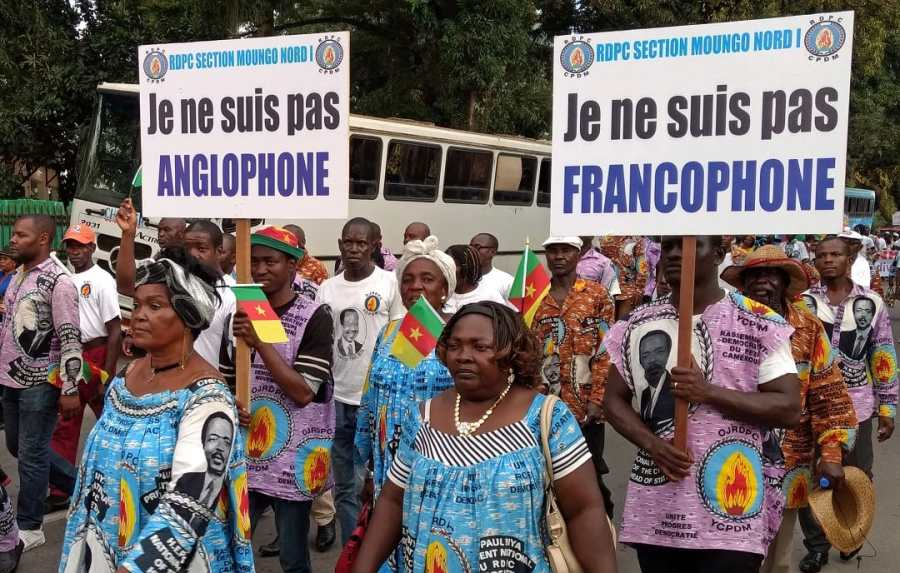 """Demonstrators carry banners as they take part in a march voicing their opposition to independence or more autonomy for the Anglophone regions, in Douala, Cameroon October 1, 2017. The banners read: """"I am not Francophone.""""(R), """"I am not Anglophone"""" (L). REUTERS/Joel Kouam - RC1761F93B50"""