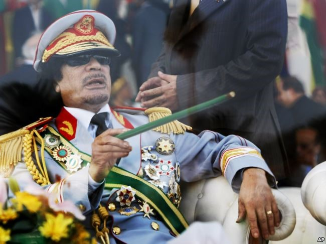 FILE - In this Tuesday, Sept. 1, 2009 file photo, Libyan leader Moammar Gadhafi gestures with a green cane as he takes his seat behind bulletproof glass for a military parade in Green Square, Tripoli, Libya. Credit/VOA