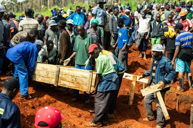 Popel carry coffins as mourners attend multiple burials at the Chimanimani Heroes Acre on March 18, 2019 in Chimanimani,  eastern Zimbabwe, after the area was hit by the cyclone Idai. - A cyclone that ripped across Mozambique and Zimbabwe has killed at least 162 people with scores more missing.