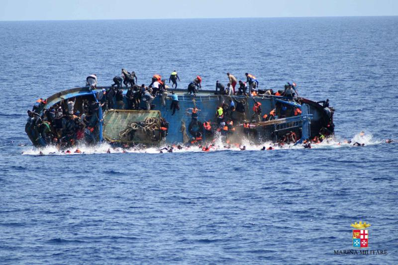 """This handout picture released on May 25, 2016 by the Italian Navy (Marina Militare) shows the shipwreck of an overcrowded boat of migrants off the Libyan coast today. At least seven migrants have drowned after the heavily overcrowded boat they were sailing on overturned, the Italian navy said. The navy said 500 people had been pulled to safety and seven bodies recovered, but rescue operations were continuing and the death toll could rise. The navy's Bettica patrol boat spotted """"a boat in precarious conditions off the coast of Libya with numerous migrants aboard,"""" it said in a statement. / AFP PHOTO / MARINA MILITARE AND AFP PHOTO / STR / RESTRICTED TO EDITORIAL USE - MANDATORY CREDIT """"AFP PHOTO / MARINA MILITARE"""" - NO MARKETING NO ADVERTISING CAMPAIGNS - DISTRIBUTED AS A SERVICE TO CLIENTS STR/AFP/Getty Images"""