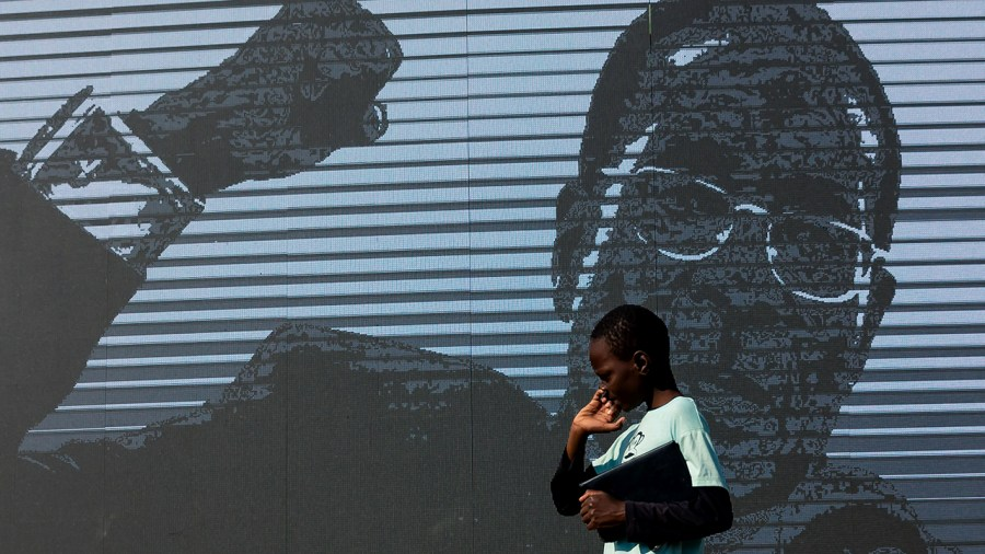 A young boy walks past a digital image of late former Zimbabwean president Robert Mugabe as his body lies in state at Murombedzi Growth Point, about 107 km northwest of Harare, Zimbabwe, on September 16, 2019, as people have been accorded the opportunity to view Mugabe's body a week after his death. - The remains of former Zimbabwe president Robert Mugabe were taken to his village for a wake on September 16, a family member said, as his final burial is prepared in about a month. Mugabe died a week ago aged 95 in Singapore, nearly two years after he was ousted in a 2017 coup that ended nearly four decades of increasingly autocratic rule. After a state funeral on September 14 in the capital Harare attended by African leaders, his body went to his rural village of Kutama, 90 kilometres (55 miles) to the west, to allow villagers to pay tribute and bid farewell. (Photo by Jekesai NJIKIZANA / AFP)