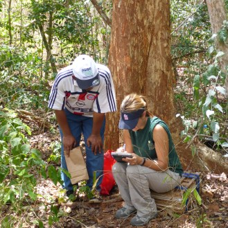 Rebecca Sucher of the Missouri Botanical Garden and Yahya Abeid recording data while sitting in front of a Karomia gigas.