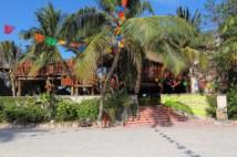 partially hidden behind palm trees is this tiki style restaurant and bar located on half moon bay between akumal beach and Yal ku lagoon
