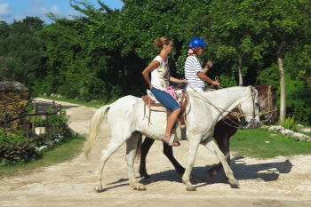 Horseback riders leaving the stables and heading to the jungle trails