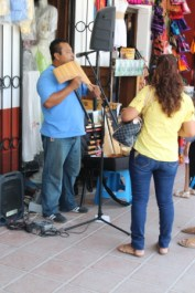 a street muscian entertaining shoppers in the main plaza