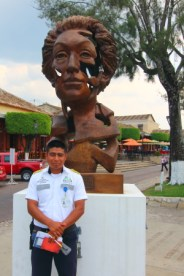 Most resort area's in Mexico have tourist police who offer a variety of services to visitors . Here is one of Comitan's finest, Senor Lopez, standing in front of a metal sculpture in the plaza.