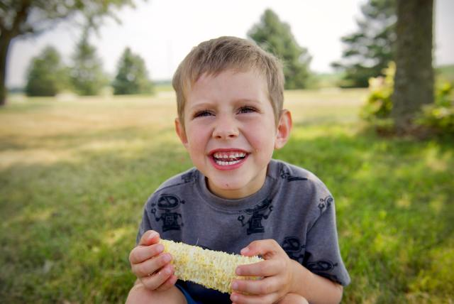 Boy eating ear of corn