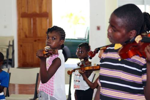In this Montserrat Music Festival photo kids learn how to play the violin at the one-week camp facilitated through the Montserrat Arts Council.