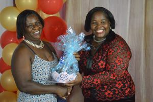 Community Care Manager Nurse Violet Brown receives a gift from Hon. Minister of Health Delmaude Ryan for being a blood donor.