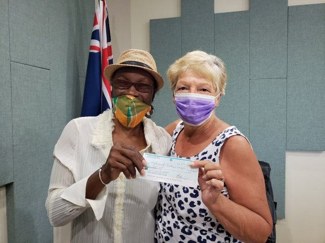 Elizabeth Piper-Wade and Margaret Ainsworth hold a check for 2000$ from the John Sweeney Montserrat Fund