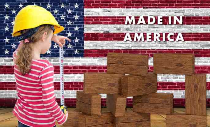 giant building blocks-timber blocks-made in america- girl, wearing a hardhat, holding a measuring tape, with a US flag background.
