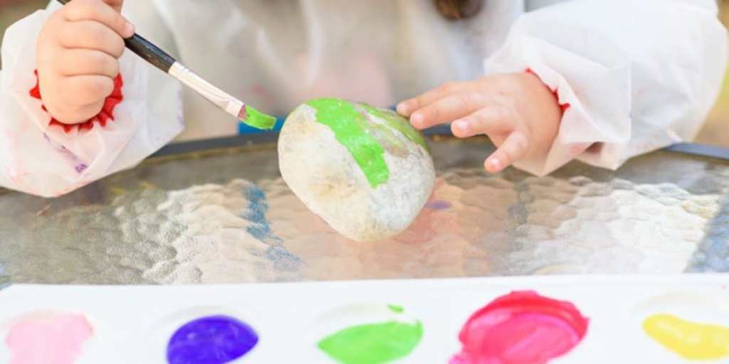 fine motor painting activities-young girl painting rocks with a brush
