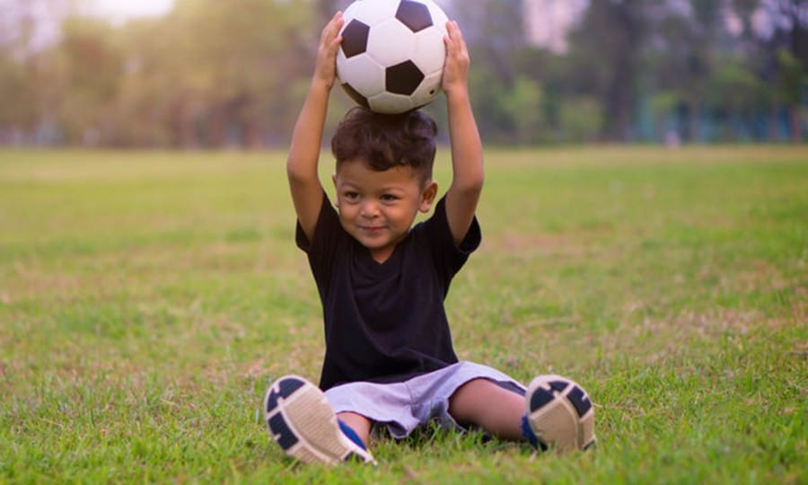 large motor activities using balls-young boy holding a soccer ball above his head in a park