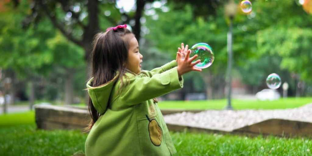 gross motor activities for preschoolers-young asian girl chasing bubbles in the park